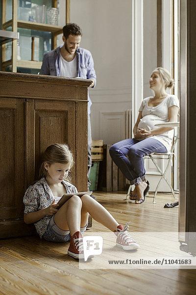 Mädchen sitzt allein und spielt Videospiel  während die Eltern chatten.