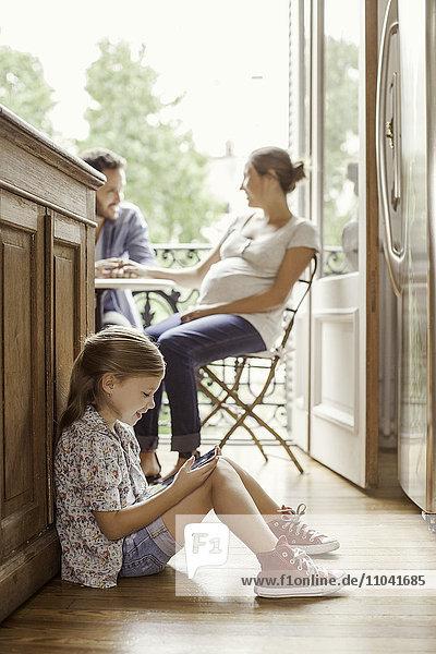 Mädchen in Videospiel vertieft  während Eltern im Hintergrund chatten