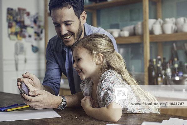 Vater und Tochter schauen gemeinsam auf das Smartphone