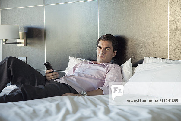 Man unwinding after work by watching TV on bed