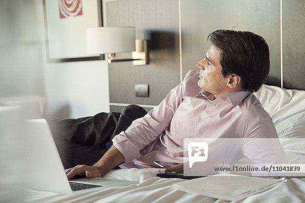 Geschäftsmann auf Hotelbett liegend mit Handy und Laptop-Computer  in Gedanken wegschauend