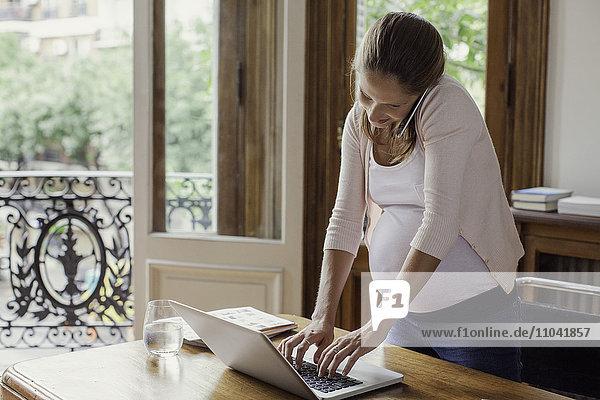 Schwangere Frau  die von zu Hause aus arbeitet