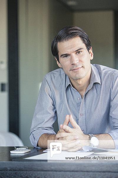 Geschäftsmann am Schreibtisch sitzend mit umklammerten Händen  Portrait