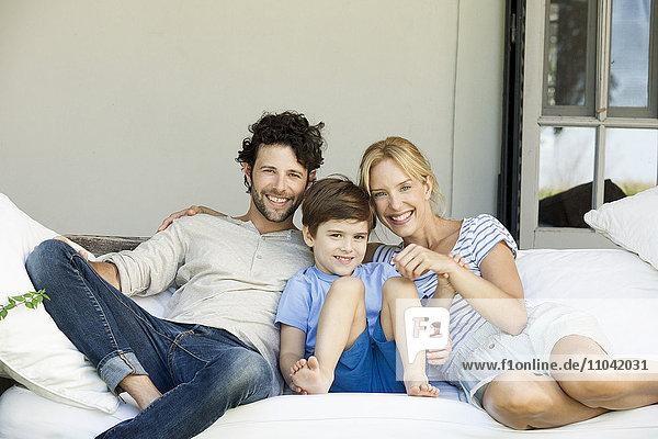 Familie mit einem Kind entspannt sich gemeinsam im Freien
