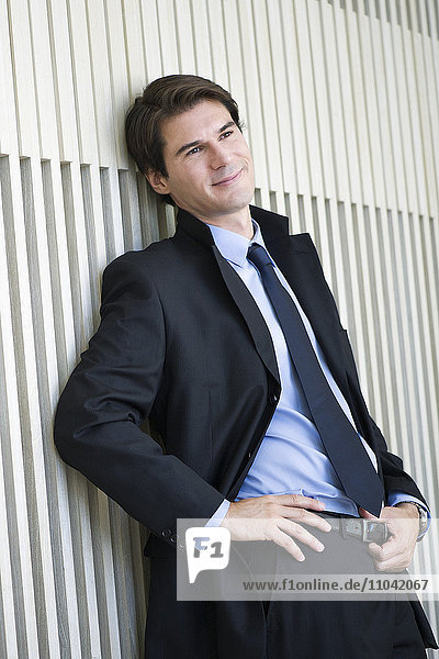 Businessman leaning against wall  looking away in thought