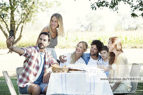 Familienposen für ein Gruppenfoto beim Picknick im Freien
