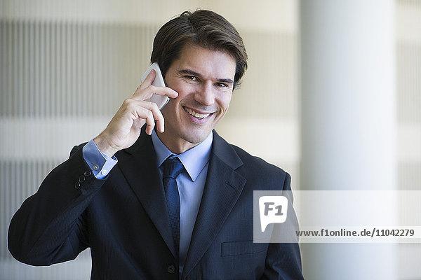 Geschäftsmann spricht am Handy  lächelt fröhlich  Porträt