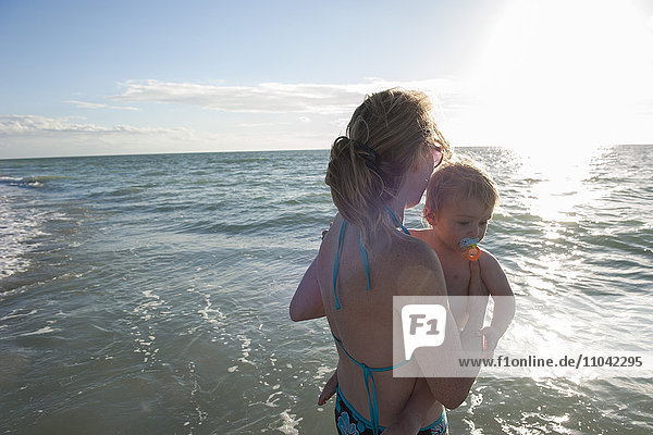 Mother wading in water with toddler boy