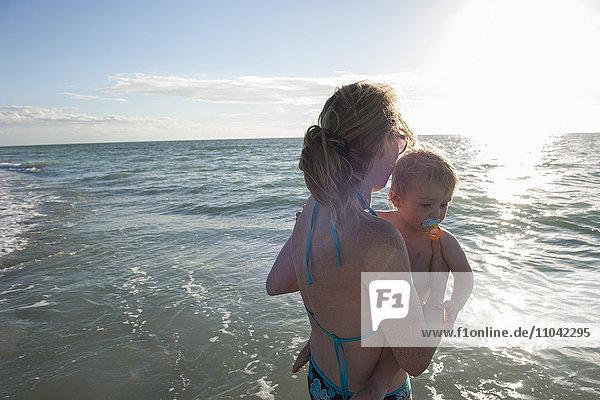 Mutter waten im Wasser mit Kleinkind Junge