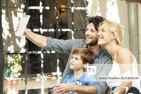 Familie mit einem Kind  das für Selfie posiert und mit einem digitalen Tablett aufgenommen wurde.