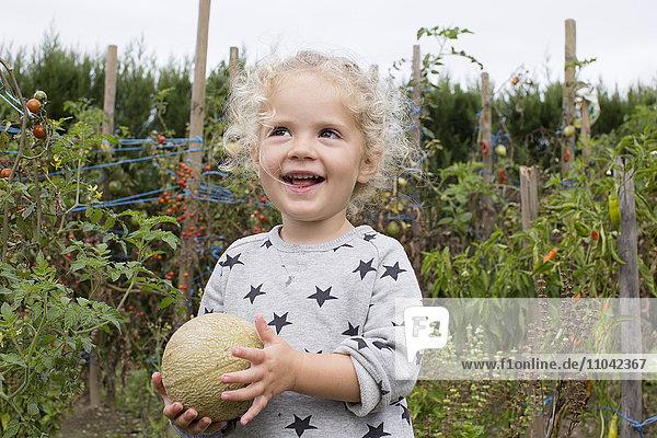 Kleines Mädchen mit Melone im Garten