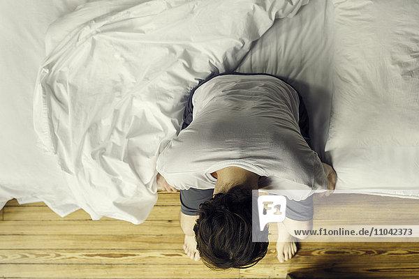 Mann auf Bettkante sitzend  Kopf haltend