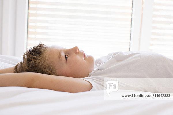 Junge entspannt auf dem Bett