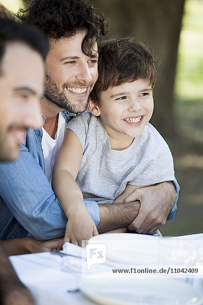 Vater und Sohn mit Freunden beim Essen im Freien