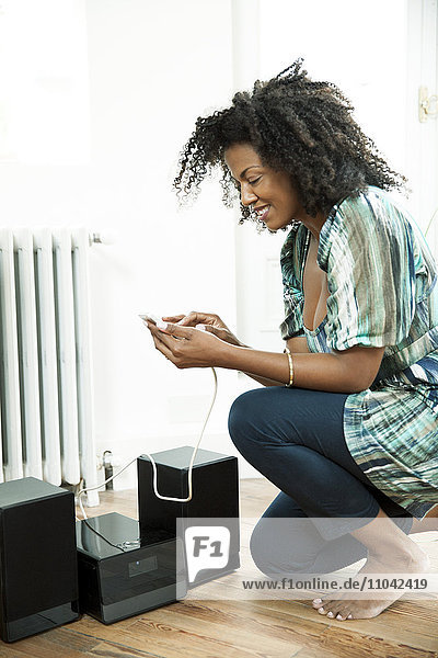 Woman playing music on smartphone over home stereo