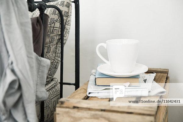Kaffeetasse und Buch auf Nachttisch