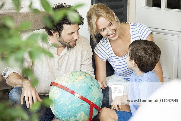 Familie mit einem Kind schaut gemeinsam auf die Weltkugel