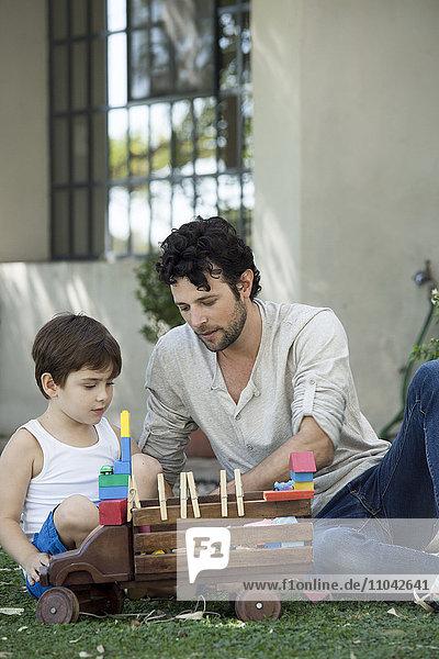 Vater und Sohn spielen mit Spielzeug im Hinterhof