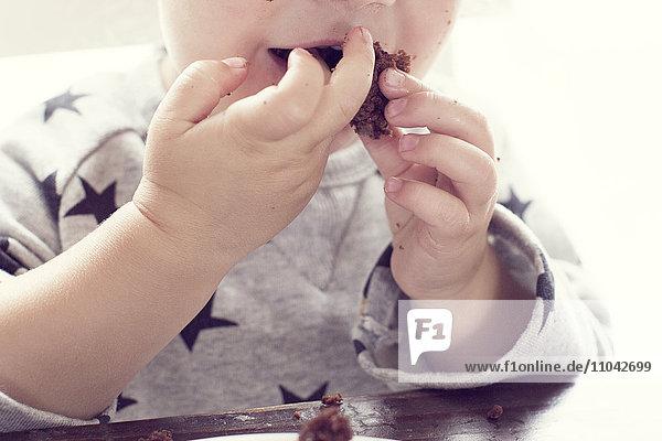 Kind isst Kuchen mit den Händen Kind isst Kuchen mit den Händen