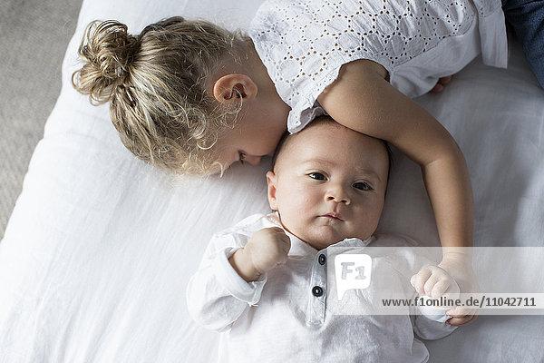 Kleines Mädchen kuschelt mit dem kleinen Bruder