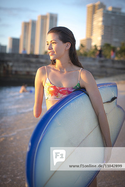 Mixed race amputee carrying surfboard on beach