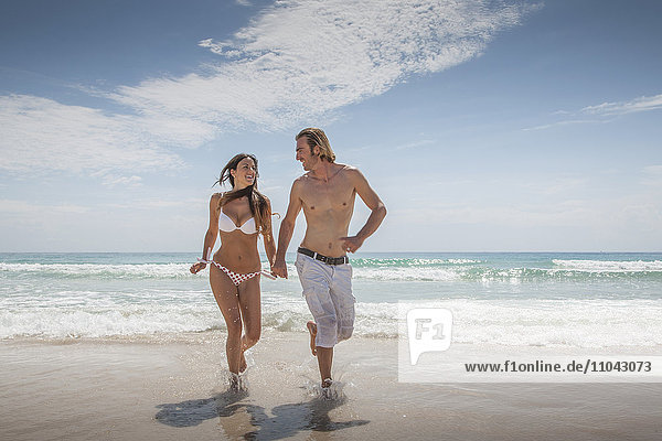 Caucasian couple holding hands and running on beach