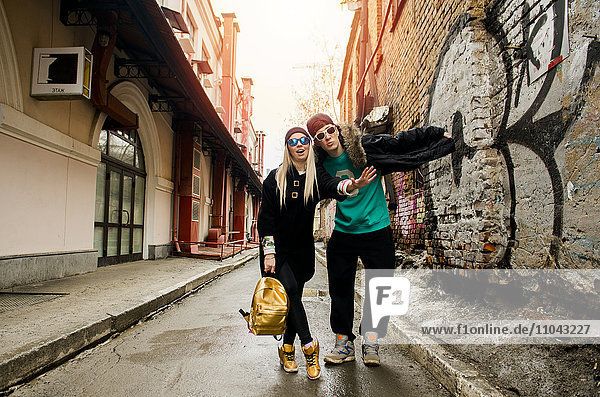 Couple gesturing stop in urban alley