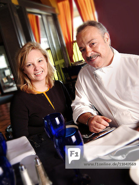 Chef and restaurant owner smiling