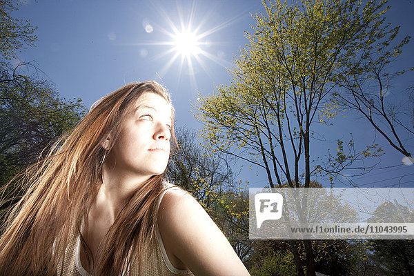 Caucasian woman looking away in sunny forest