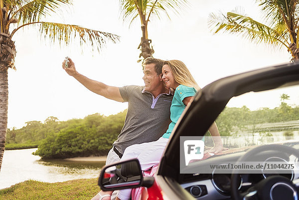Caucasian couple taking selfie on convertible