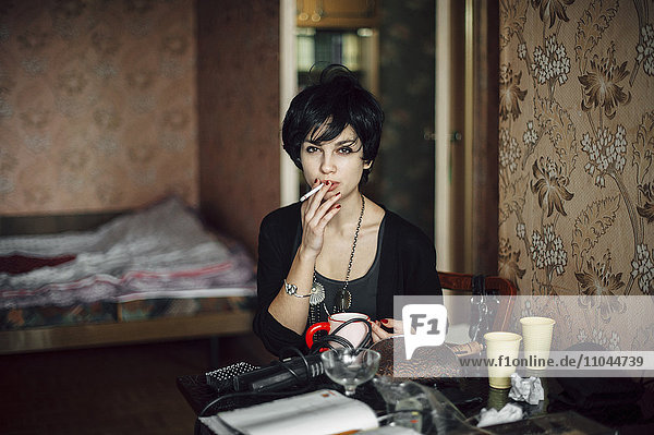 Caucasian woman smoking cigarette in bedroom