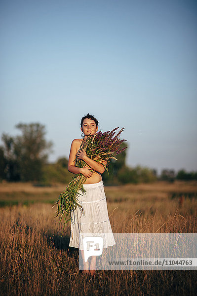 Caucasian woman carrying flowers in rural field