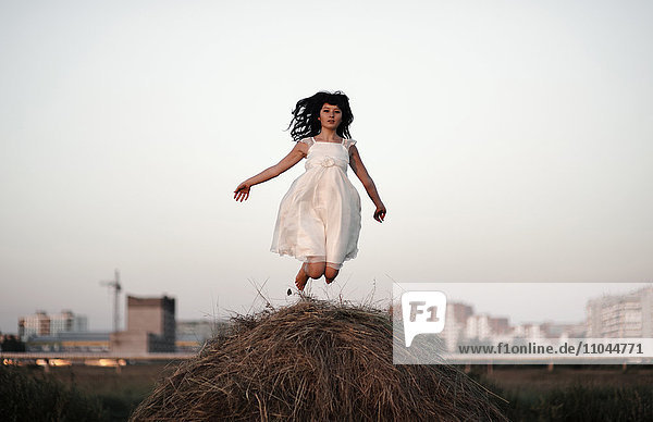 Caucasian woman jumping on haystack