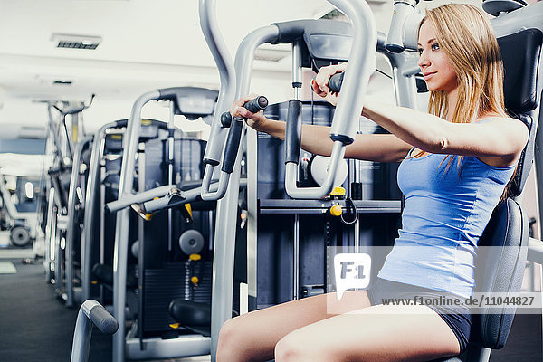 Woman using weight machines in gym