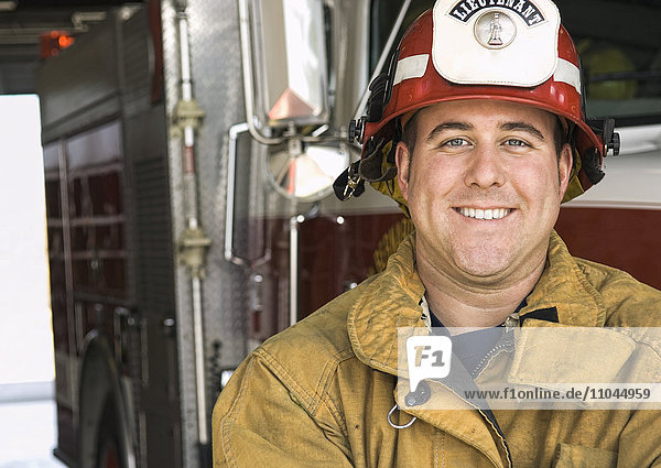 Caucasian firefighter smiling near fire truck