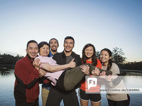 Chinese family posing near lake outdoors
