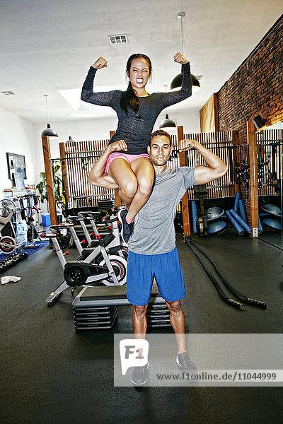 Man holding girlfriend in gymnasium