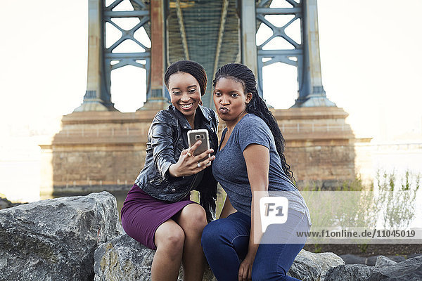 Black women posing for selfie at bridge