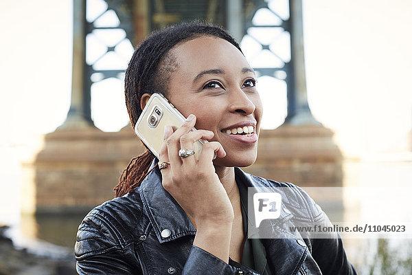 Smiling Black woman using cell phone at bridge