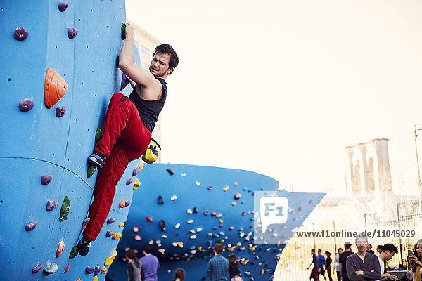 Caucasian man climbing outdoor climbing wall