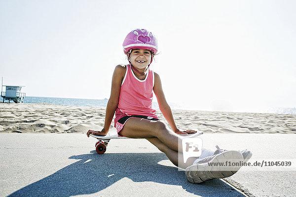 Mixed race girl sitting on skateboard at beach