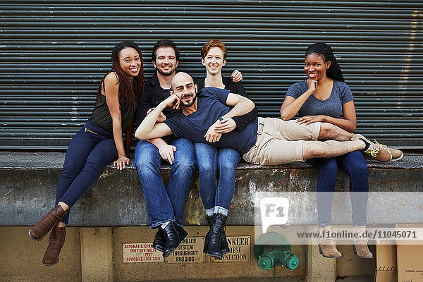 Man laying in laps of friends on loading dock