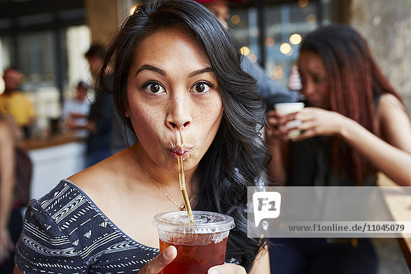 Woman drinking cold drink with straw in cafe