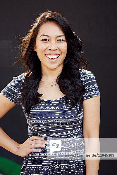 Laughing Pacific Islander woman standing with hand on hip