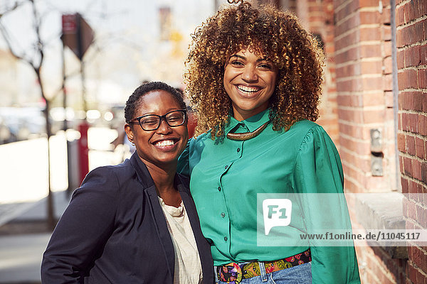 Smiling Black women posing on city sidewalk