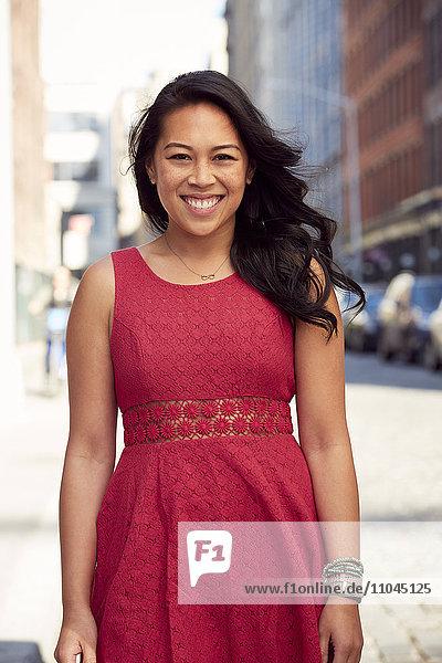 Pacific Islander woman smiling on city sidewalk