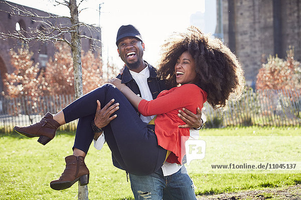 Man carrying woman and laughing