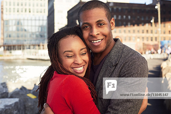 Black couple hugging at waterfront