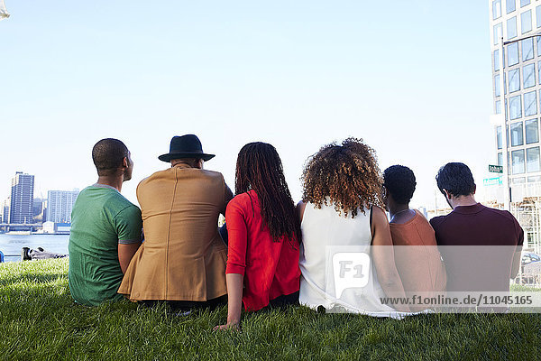 Friends sitting in grass at waterfront