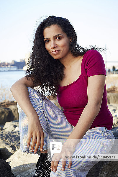 Mixed Race woman sitting on rock at waterfront